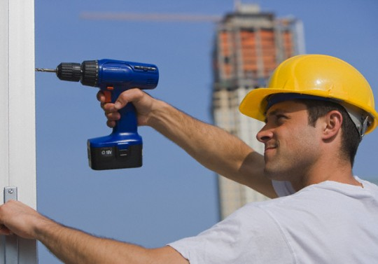 Construction worker using cordless drill