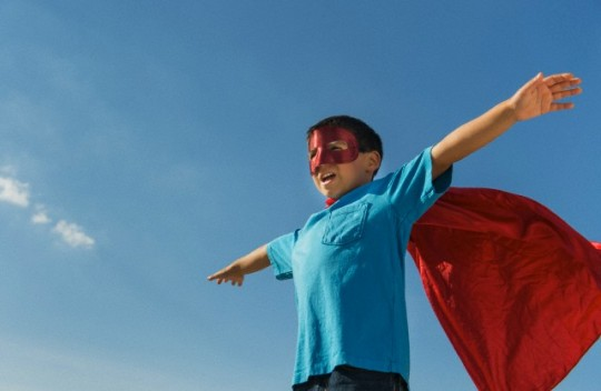 Boy (6-7) in superhero costume under blue sky