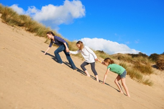 Three girls climbing up sand dune